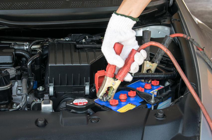 automotive technician charging vehicle battery